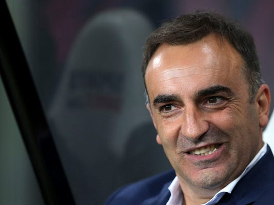 FILE - In this file photo dated Wednesday, Sept. 23, 2015, Sheffield Wednesday's manager Carlos Carvalhal awaits the start of the English League Cup third round soccer match between Newcastle United and Sheffield at St James' Park, Newcastle, England. Carvalhal seems to be giving new energy to revitalize Swansea and is fast becoming a new darling of British soccer with his colorful analogies, infectious enthusiasm and positive outlook.(AP Photo/Scott Heppell, FILE)