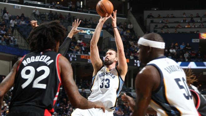 Memphis Grizzlies Marc Gasol, center, take an outside shot flanked by Toronto Raptors Lucas Nogueira, left, and Zach Randolph, right.