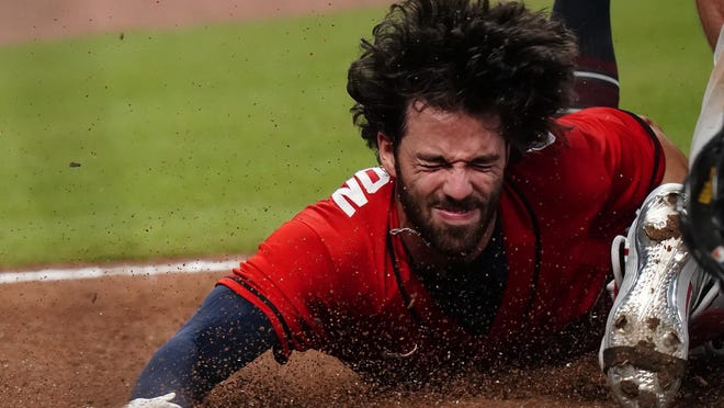 The Braves' Dansby Swanson dives into home plate and is tagged out by Philadelphia Phillies' Andrew Knapp, during the ninth inning Sunday in Atlanta.