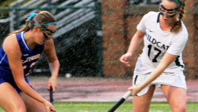 Novi's Willow Guenther (right) vies for possesion against Ladywood's Jillian Jacobs (left) in the rain.