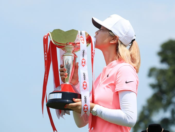 Michelle Wie celebrates with the winner's trophy after