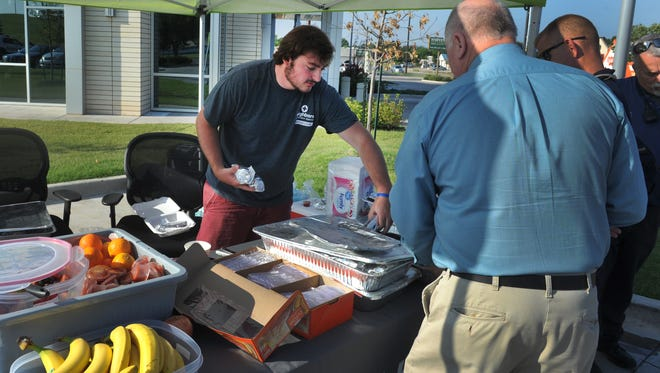 Neighbors Emergency Center brand ambassador Josh Monkres serves breakfast Tuesday morning during the center's Burritos for Badges event in their parking lot at the corner of McNiel Avenue at Kell East Boulevard. Wichita Falls police, fire and Wichita County deputies were treated with breakfast burritos, fruit, coffee and juice.
