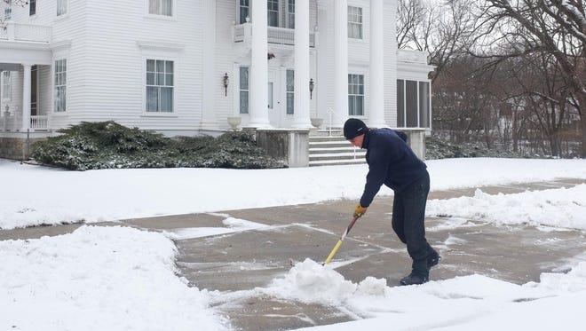 Al Searle shovels late season snow in Mason City, Iowa, Monday, March 23, 2015.