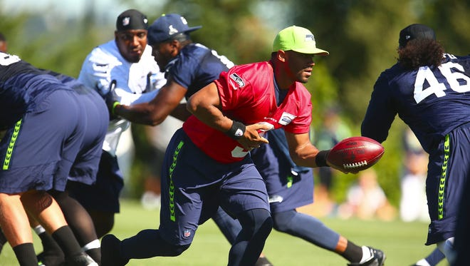 Seattle Seahawks quarterback Russell Wilson runs a play during NFL football training camp Friday, Aug. 7, 2015, in Renton, Wash.