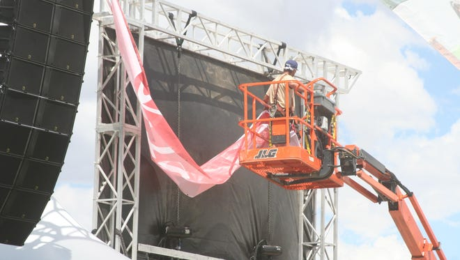 Workers prepare a backdrop for a stage for the 2015 Night in the Country music festival.