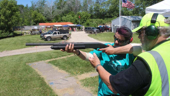 Gina Zarletti, an ovarian cancer survivor who lives in Racine, gets trapshooting instruction from Ron Oleszak of Big Bend during Take Aim at Cancer event at Schultz Resort Rod & Gun Club in Muskego.