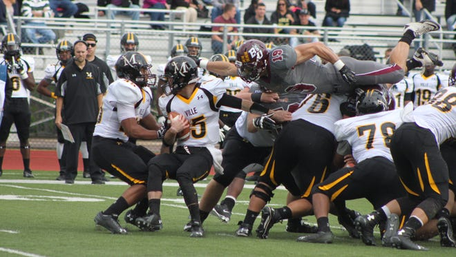Bloomsburg University and Central York grad Eric Schwartz leaps over the Millersville offensive line in a game earlier this season.