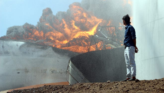 A man looks on as fire ignites in an oil storage tank at the main oil refinery in the southern port city of Aden, Yemen on Jan. 12, 2019.