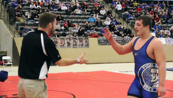 Tucker Mueller of Simon Kenton is congratulated by head coach Steve Kaiser after a win in the KHSAA state wrestling meet Feb. 22 at Alltech Arena in Lexington.