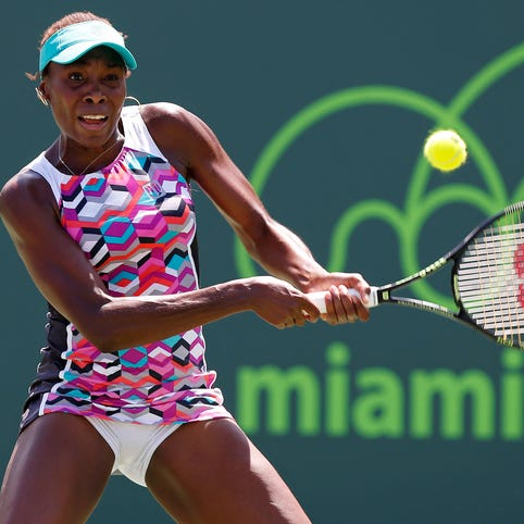 Venus Williams hits a backhand against Caroline Wozniacki