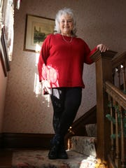 Bonnie Maher, owner, poses on the stairs inside the Dreams of Yesteryear Bed and Breakfast, which some have said has a resemblance to the show Gilmore Girls.