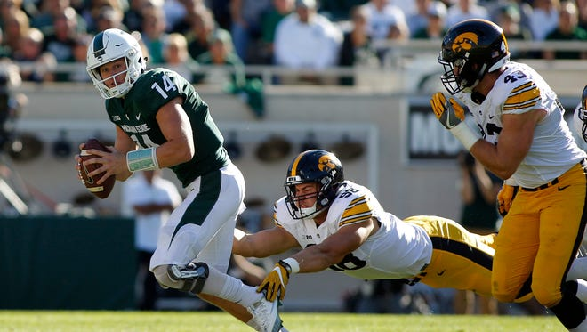 Iowa's Anthony Nelson trips up Michigan State quarterback Brian Lewerke, as Iowa's Josey Jewell, right, pursues during the first half Saturday, Sept. 30, 2017 in East Lansing.