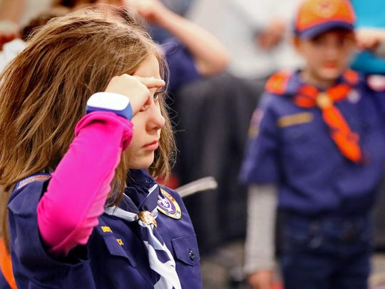Cassie Vincent and eight other girls give the Cub Scout salute for the Pledge of Allegiance at the start of the first meeting of Den 7, Pack 505, one of two new girl Cub Scout dens to form in the area.
