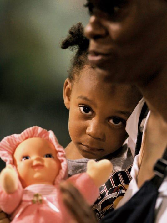 Archive photo: After evacuating New Orleans, Violet Riles, 2,  held her doll as she nestled in her mother Monique Riles' arms shortly after arriving in El Paso.