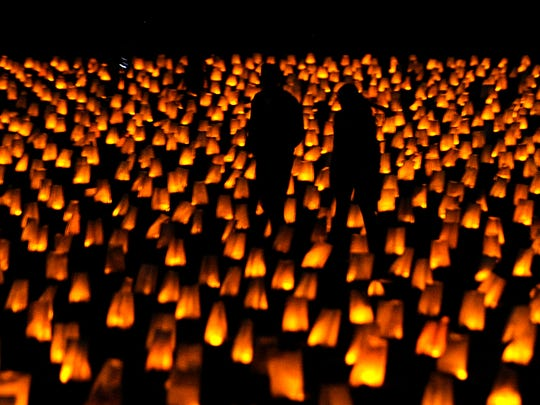 People walk among 5,000 luminaries that were displayed on a field adjacent to the Confederate Cemetery at Carnton Plantation on Sunday Nov. 30, 2014. To commemorate the 150th Anniversary of the Battle of Franklin.