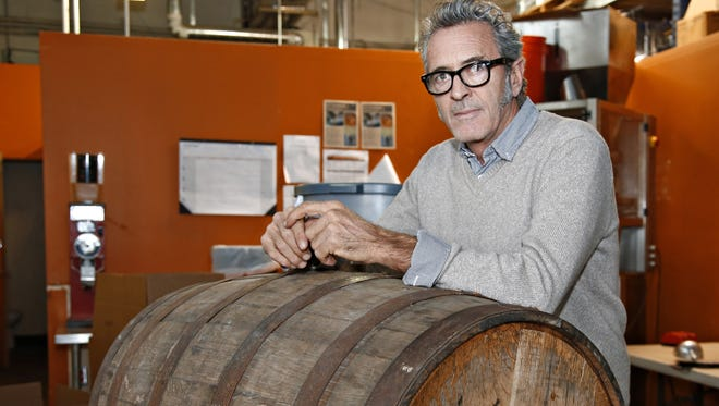 Patrick O'Malley stands in front of a bourbon barrel full of raw coffee beans at Espresso Italia.