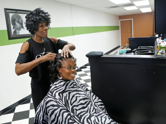 Debra Wilburn talks with Tenecia Waddell as she styles her hair October 10, 2015 at Onyx Styling & Braiding Salon, 20 N. Earl Ave. in Lafayette.