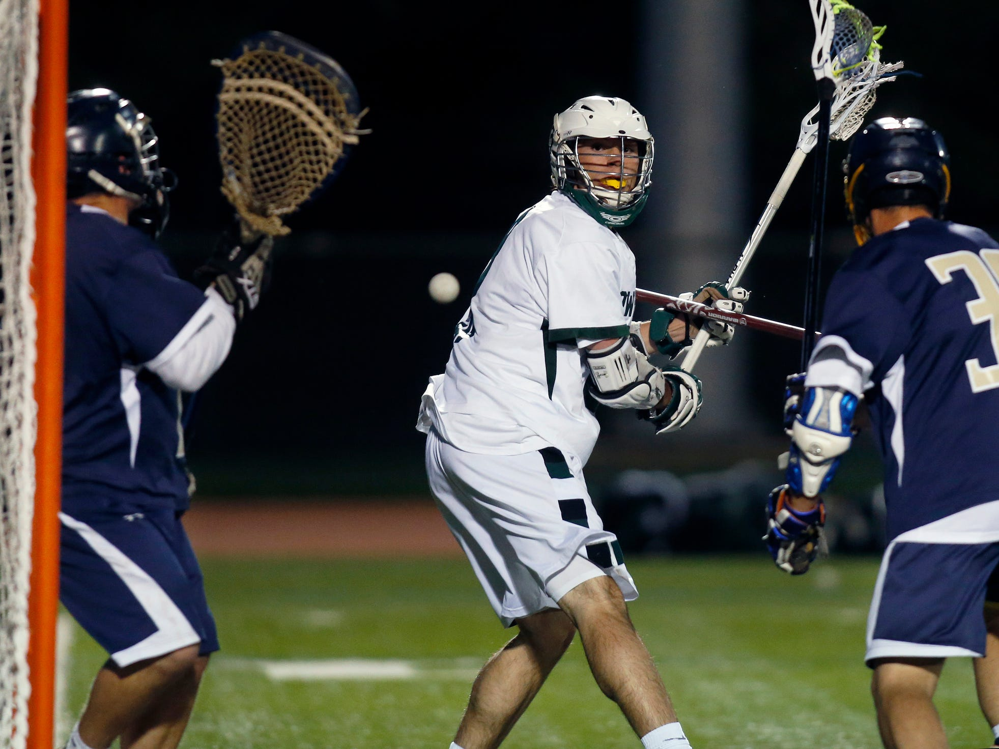Tower Hill's Andrew Pettit turns to watch his back-to-the-goal shot find its way past Delaware Military Academy goalie Alex Kurfuerst (left) and defender Jonathan Howell in the second quarter of Tower's 12-9 comeback win at home Friday.