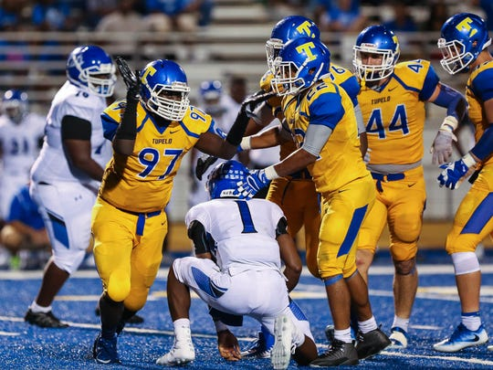 Tupelo's Janson Nabors (97) reacts after sacking Meridian's Tevarrius Adams (1) during a regular season game at Tupelo High on August 18, 2017.