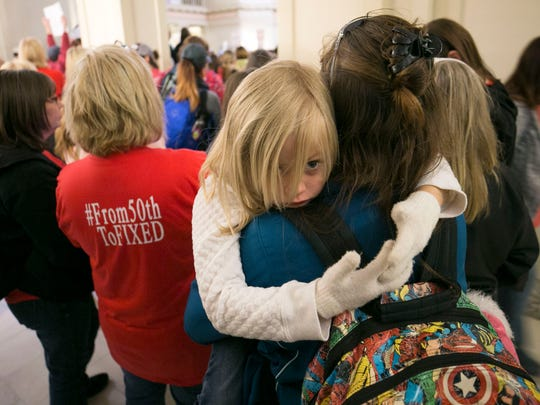 Kim McCreery a seventh grade English teacher in Tecumseh, Okla., holds her daughter, Keira McCreery, 5, as they rally with other teachers inside of the Oklahoma state capitol on the second day of the Oklahoma teachers walkout, at the capitol in Oklahoma City April 3, 2018.