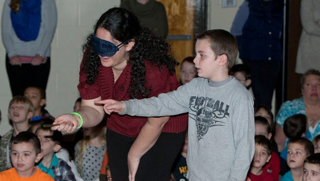Second-grader James Doherty, 8, helps his blindfolded teacher, Leah Posner, during a game about teamwork at Whiting Elementary School in Manchester, N.J.