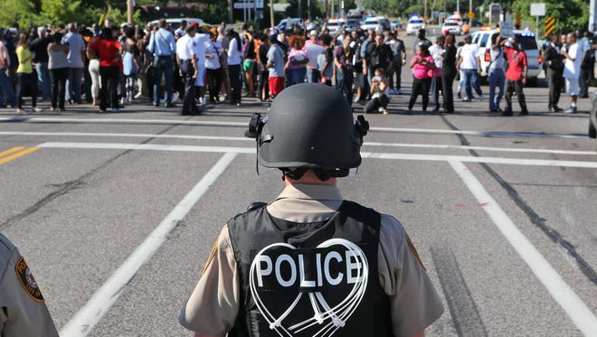 A line of police wait for demostrators in Ferguson, Mo., on Wednesday.