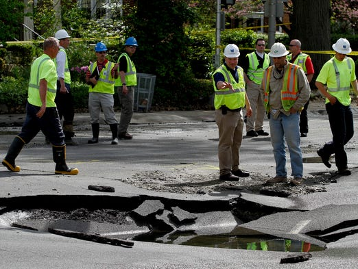 Officials investigate the buckled road following a water main break at Eastern Pkwy. and Baxter Ave. Apr. 24, 2014