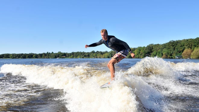 Trevor Grindland, 21, crosses over to surf the other side of a wake Saturday morning on the Mississippi River north of the Sartell Dam. Grindland, who's ranked No. 10 in the world in his division, said he sees the sport as a hobby that could pay for himself. He's a senior majoring in mechanical engineering at North Dakota State University.