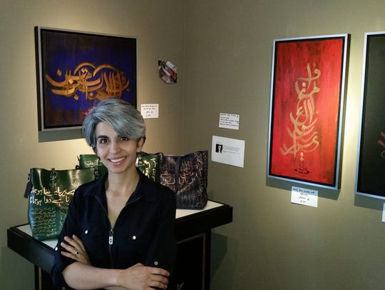 The artist Arshia Qasim stands before some of her paintings