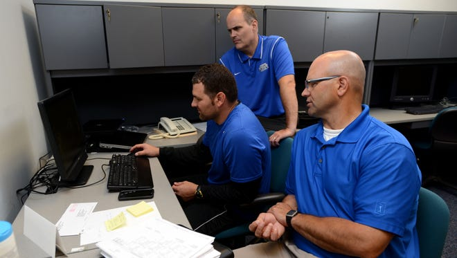 UWF football coach Pete Shinnick, standing, assistant coach Steve Saulnier, right, and offensive coordinator Jammie Deese review film as they begin building the Argonauts' program ahead of their first season in the fall of 2016.