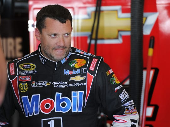 Driver Tony Stewart watches his crew make adjustments on his car during NASCAR practice at the Indianapolis Motor Speedway on July 27, 2013.
