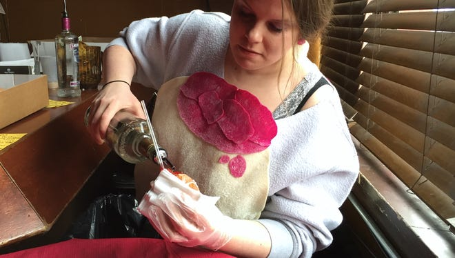 Kayla DeWitt of Ferndale, MI, serves up Paczki Bombs at Small's Bar in Hamtramck, MI on Tuesday, Feb. 9, 2016.