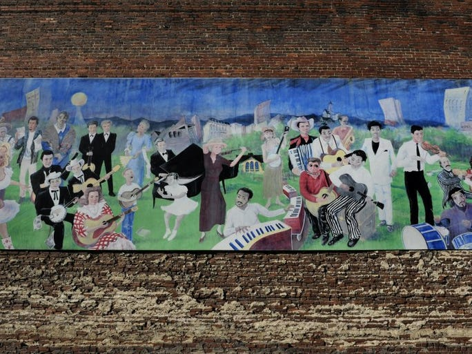 A portion of the 12 x 64-foot Knoxville Music History Mural in the Old City shows 41 music artists who were either born in the Knoxville area or spent important years making music in the city. The far left and far right portions of the mural are not shown. Commissioned in 2000 by Keep Knoxville Beautiful, the mural was recently painted over by the owner of the building at 118 E. Jackson Ave. It was designed by students of Laurel High School and painter Walt Fieldsa.