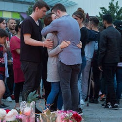 People gather to read tributes among the flowers and candles near to the Olympia shopping center where a shooting took place leaving nine people dead the day before in Munich, Germany, on July 23, 2016.