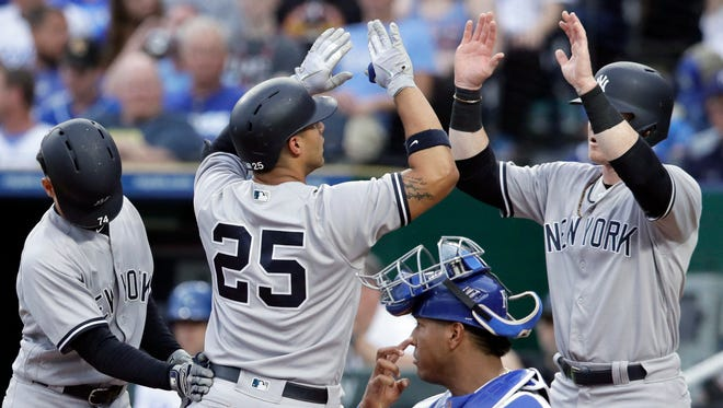 New York Yankees' Gleyber Torres (25) celebrates his three-run home run with teammates Ronald Torreyes, left, and Clint Frazier, right, next to Kansas City Royals catcher Salvador Perez (13) during the fourth inning of a baseball game at Kauffman Stadium in Kansas City, Mo., Saturday, May 19, 2018.