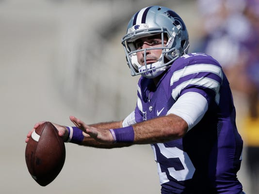 Kansas State quarterback Jake Waters (15) looks for a receiver while scrambling from the pocket during the second half of an NCAA college football game against Texas in Manhattan, Kan., Saturday, Oct. 25, 2014. Waters threw for 224 yards in the game. Kansas State defeated Texas 23-0. (AP Photo/Orlin Wagner)