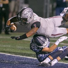 Chandler Hamilton running back Ari Johnson (1) leaps over Phoenix Pinnacle defender Liam Castle and scores a touchdown during a high school football game on Friday, Sept. 12, 2014, in Phoenix.