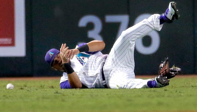 Arizona Diamondbacks' David Peralta grabs his wrist after being injured trying to catch a base hit by Colorado Rockies' Rafael Ynoa during the fourth inning of a baseball game, Thursday, Oct. 1, 2015, in Phoenix. Peralta left the game at the end of the inning.