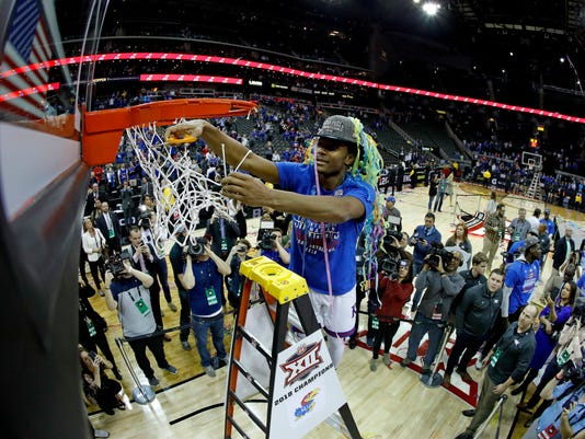 Kansas' Devonte' Graham cuts the net after winning the NCAA college basketball championship game against West Virginia in the Big 12 men's tournament Saturday, March 10, 2018, in Kansas City, Mo. Kansas won 81-70. (AP Photo/Charlie Riedel)