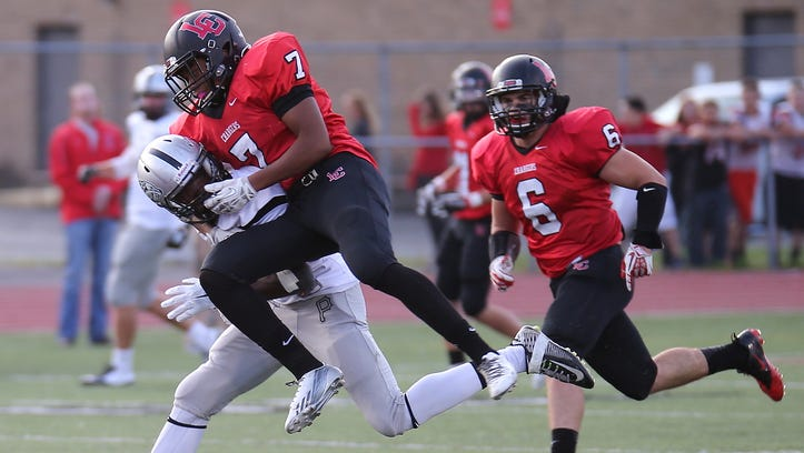 Plymouth's Vctor Abraham is tackled hard by Livonia Churchill's Jamal Allen. At right for the Chargers is Aaron Kerr (No. 6).