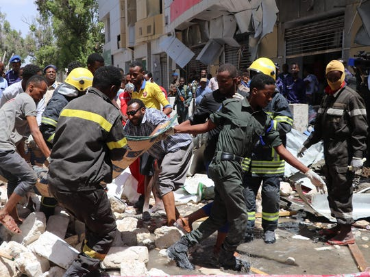 Emergency rescue staff carry the body of a victim over