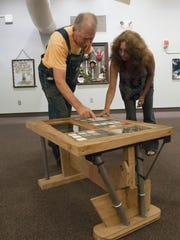 Pensacola State College art student Mark Robinson, left, describes his inspiration for his rustic trestle-type coffee table to fellow artist and PSC student Mary Lynn Grande, while viewing the art show featuring repurposed items from the Pensacola ReStore.