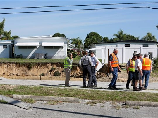 Emergency workers assess an area where a 60-foot-wide sinkhole opened on Wednesday in a Pinellas County utilities easement bordering the south side of the Tarpon Shores Mobile Home Park  in Tarpon Springs, Fla. Crews evacuated a half dozen residents whose homes were in close proximity to the sinkhole, according to authorities at the scene.