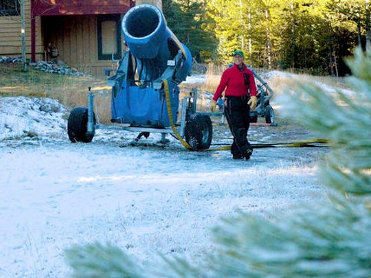 FILE - In this Nov. 4, 2016, file photo, Michelle Vona with the Breckenridge Nordic Center checks a mobile snowmaking gun on a trail near the center's lodge near Breckenridge, Colo. Autumn snow has been scarce in the Rocky Mountains, forcing some ski areas to push back opening day and raising concerns about how much water will be available next spring for the Colorado River. But the first big storm of the season is expected to blow into Colorado and Utah on Thursday, Nov. 17, 2016.