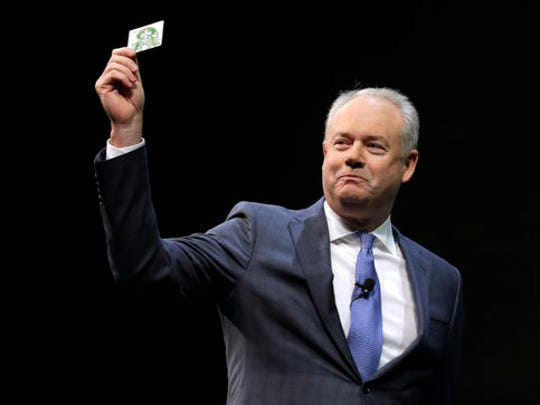 FILE - In this Wednesday, March 23, 2016, file photo, Kevin Johnson, president and chief operating officer of Starbucks Corp., holds up one of the coffee company's prepaid Visa debit cards, at the company's annual shareholders meeting in Seattle. Starbucks announced Thursday, Dec. 1, 2016, that CEO Howard Schultz is stepping down from the coffee chain that he joined more than 30 years ago, and that Johnson will become chief executive as of April 3, 2017. Schultz will become executive chairman on that date to focus on innovation and social impact activities, among other things.