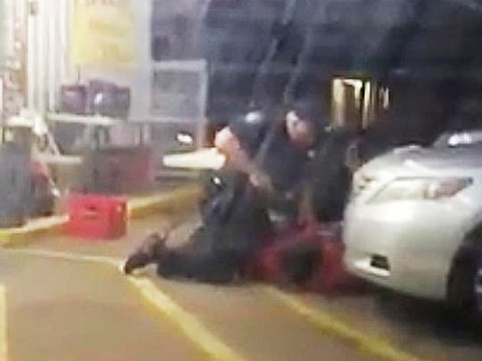 FILE - In this Tuesday, July 5, 2016 image made from video, Alton Sterling is restrained by two Baton Rouge police officers, one holding a gun, outside a convenience store in Baton Rouge, La. Moments later, one of the officers shot and killed Sterling, a black man who had been selling CDs outside the store, while he was on the ground. A day later, a white police officer shot and killed Philando Castile during a traffic stop in a suburb of Minneapolis. Coming after several similar cases in recent years, the killings rekindled debate over policing practices and the Black Lives Matter movement.