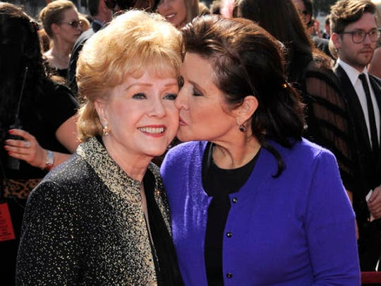 "FILE- In this Sept. 10, 2011, file photo, Debbie Reynolds, left, and Carrie Fisher arrive at the Primetime Creative Arts Emmy Awards in Los Angeles. Reynolds, star of the 1952 classic ""Singin' in the Rain"" died Wednesday, Dec. 28, 2016, according to her son Todd Fisher. She was 84."