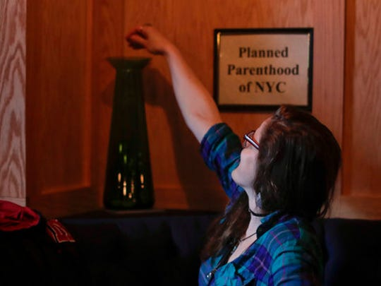 A customer drops a token into a vase designated for Planned Parenthood, one of several situated around Coup for customers to choose which organization they want their portion of the bar's profits to go, Tuesday, April 25, 2017, in New York. As a response to the Trump Administration, the bar in Manhattan's East Village offers patrons the chance to put their money where their politics are.