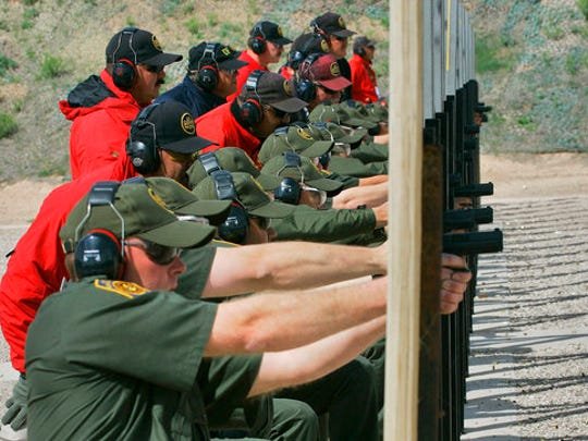 FILE - In this April 5, 2007 file photo, Border Patrol agent recruits practice small arms firing as senior agents, in red, watch at the Border Patrol Academy in Artesia, N.M. U.S. Customs and Border Protection, the parent agency of the Border Patrol and of Office of Field Operations, is taking steps to hire more agents and customs officers. President Donald Trump has ordered 5,000 new Border Patrol positions.