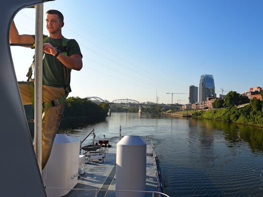 David Miget climbs down from the roof of the pilothouse as the James Paul Ayers towboat passes through Nashville on the Cumberland River.